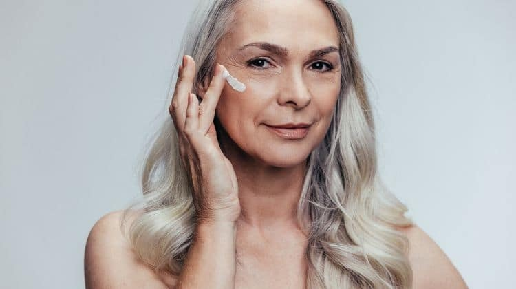 Mature woman putting on skin care cream