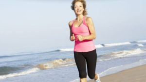 Healthy older woman running at the beach